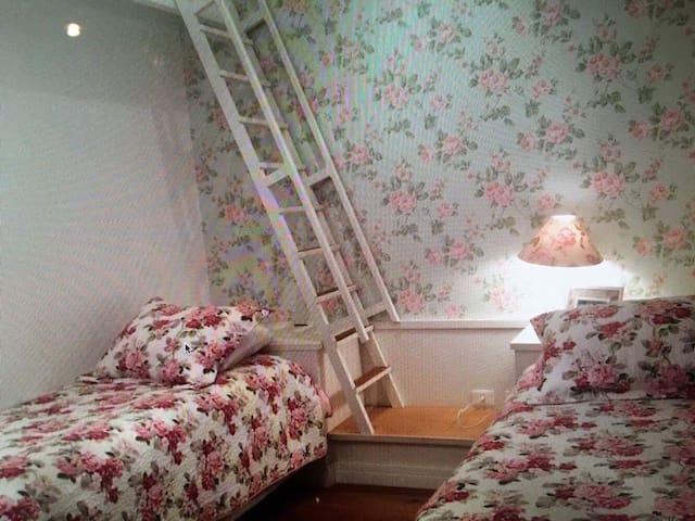 Quarto 04: Suíte com duas camas de solteiro, uma bicama e ainda mezanino com dois futons. Tem aquecedor preso na parede, mesa de estudos com duas cadeiras e espelho inteiro. Banheiro com box e parte da pia separada da parte do chuveiro.