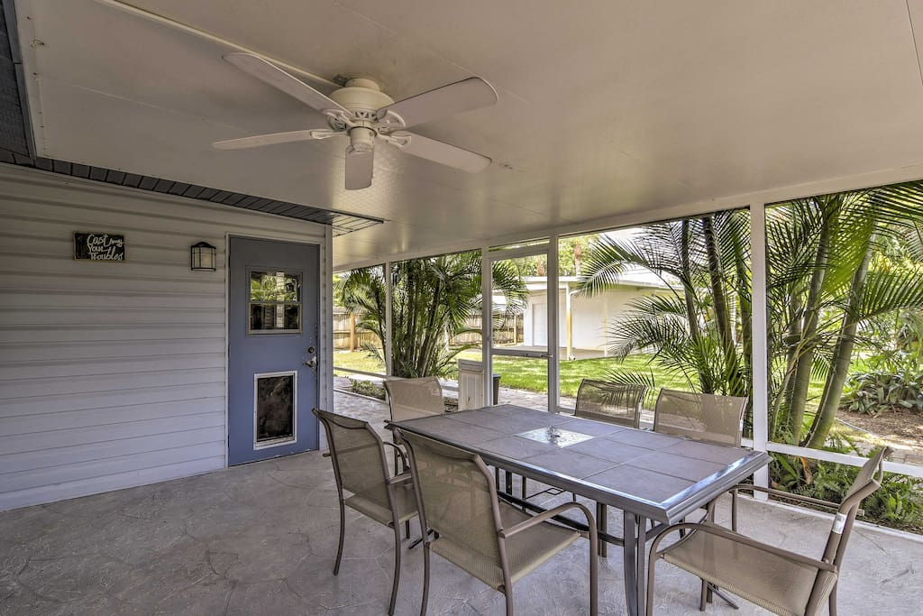The coastal home features a screened-in porch with a TV, ceiling fan, dining set and doggy door.
