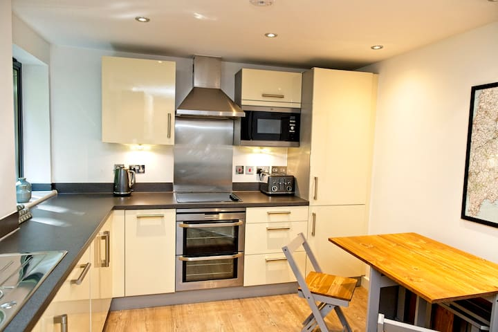 Fully fitted modern kitchen with double oven, fridge, freezer, dishwasher, microwave, kettle, toaster and caffetiere. Folding dining table with four chairs.