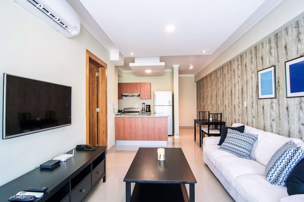 The Spacious Livingroom comes with an Open Kitchen, Lounge Area, Balcony with city view and seating area, TV + Cable, WIFI and AC