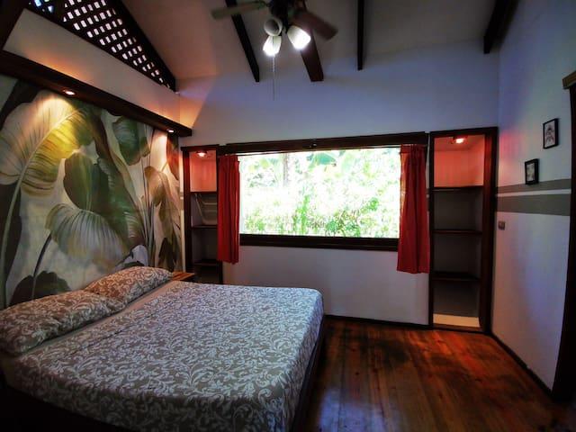 Cuarto con cama matrimonial, abanico de techo, mosquiteros a puertas y ventanas.