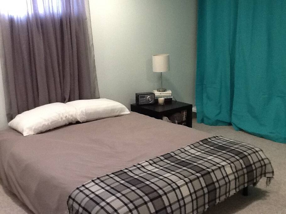 Bedroom 1, the Poolside Room, is a large room with a queen bed and a bonus loft with two twin mattresses, curtained off for privacy. Sleeps 4 guests.
