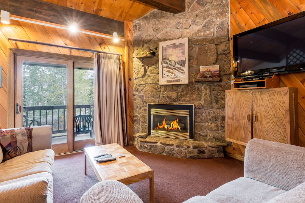 """This lodge-style living area features a cozy gas fireplace, 55"""" flat screen TV, and complimentary Wi-Fi."""