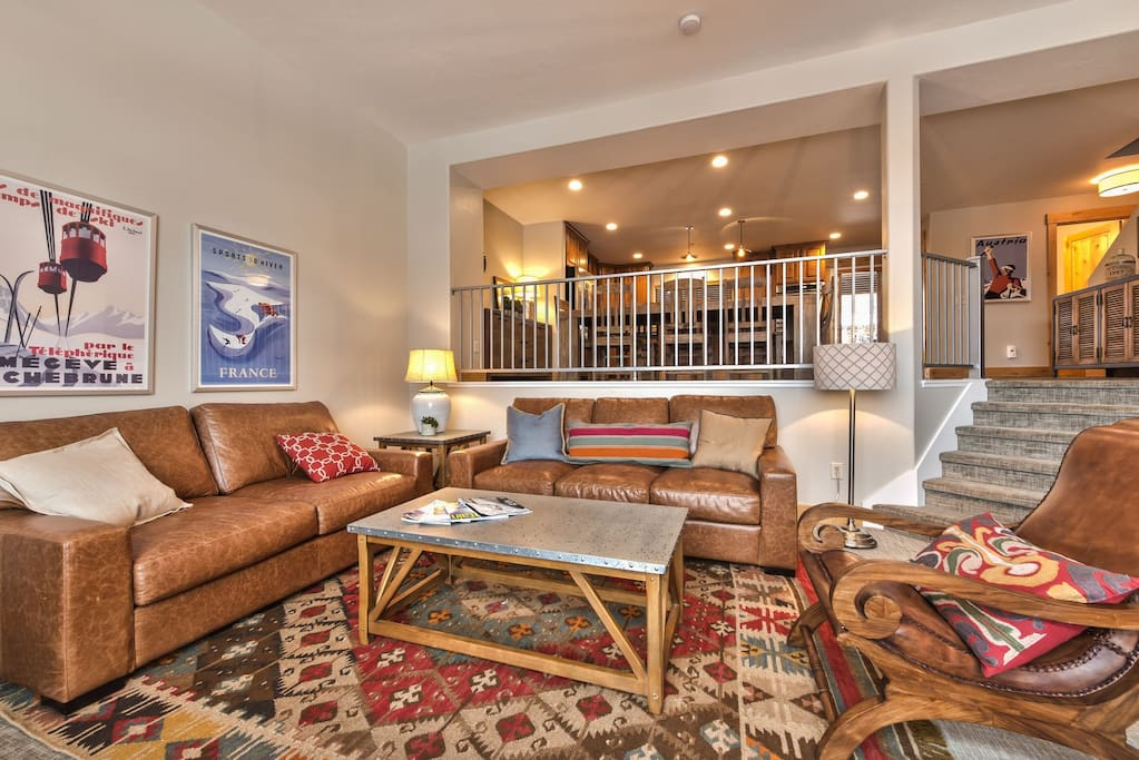 """Main Level - Living Room with Comfortable Leather Furnishings, 60"""" LG Smart TV, Blu-ray DVD, Gas Fireplace, Kitchen and Dining Area"""