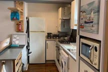 Fully equipped kitchen looking directly from bathroom area. Fridge freezer located at far side of kitchen