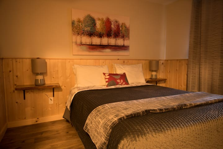 Cozy queen bed with pine accent walls and handcrafted cedar night stands.