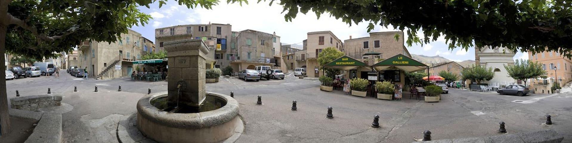 La place centrale de Spéloncato. Le bar-restaurant familial Le Gallieni