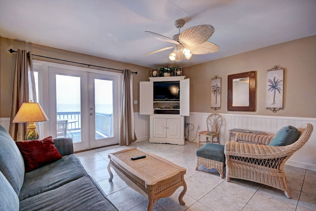 The spacious living room features double doors leading to one of the three balconies with expansive views of the gorgeous Gulf of Mexico.