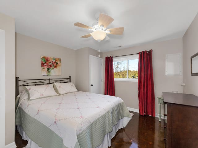 The 3rd bedroom has a queen size bed and dresser with a view of the farm and hazelnut orchard.