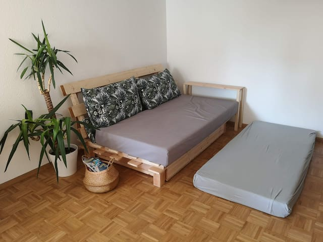 """Living room: The sleeping sofa consists of two comfortable mattresses, """"sitting"""" (200x100) and """"backrest"""" (two pieces of 100x90). For sleeping, the two backrest pieces are put on the ground and joint together using a fitted sheet."""