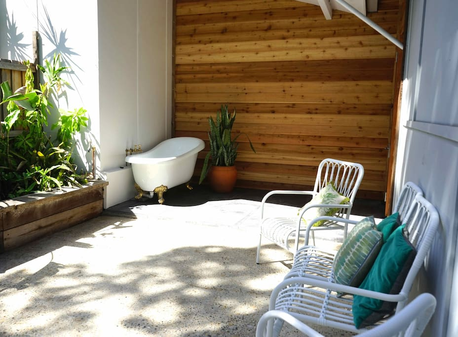 Private courtyard with tropical gardens and claw foot bath