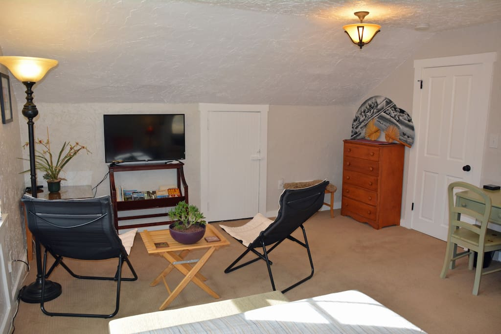 """Lounge area in bedroom with 40"""" TV with Roku so you can stream your favorite content. Also, there is a dresser and desk in this space."""