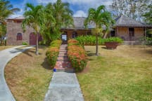The front entrance to Villa Piton is a vibrant tile walk accentuated with tropical trees, flowers and plantings.