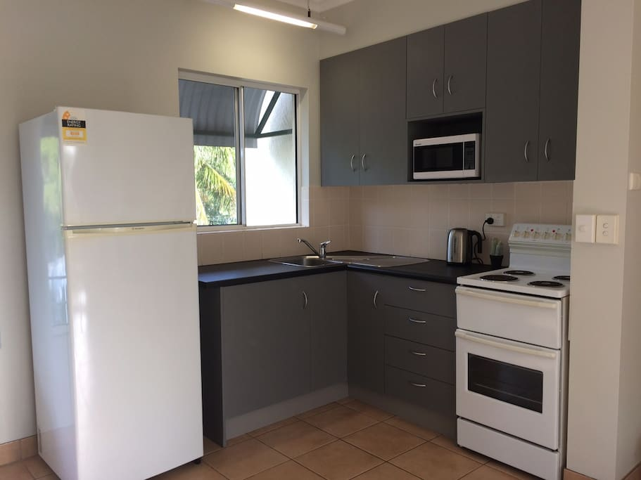 Kitchen including fridge, stove, oven microwave as well as cooking utensils to cook up a storm