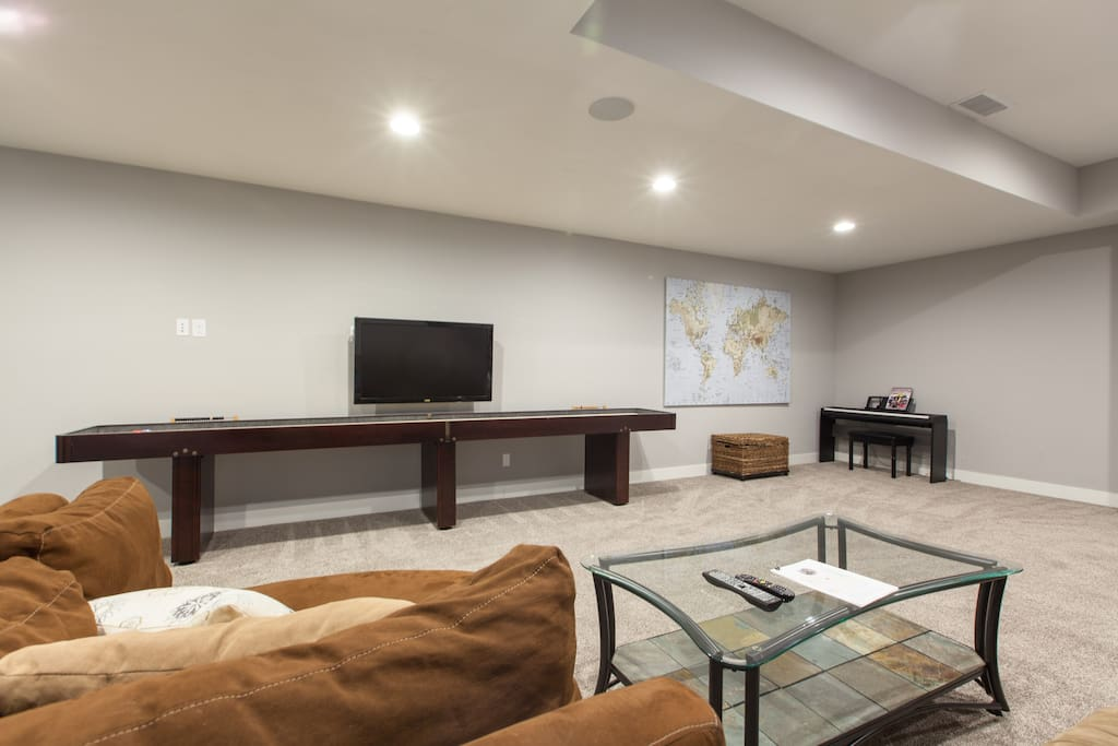 Spacious and private basement living room with shuffleboard table, TV, games and more. TV has cable and internet access for Netflix