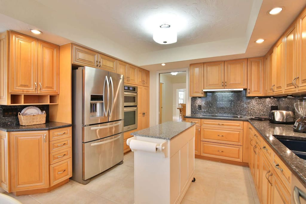 Beautiful custom kitchen with new stainless appliances, tile flooring and solid stone counters.