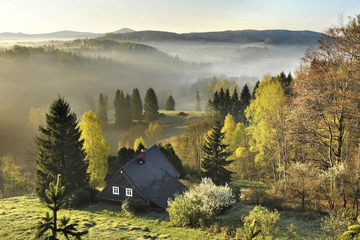 Vlčí Hora cottage in wilderness with distant view