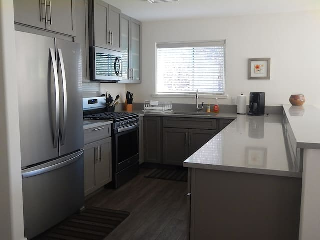 Newly remodeled kitchen with quartz countertops, gas stove and new flooring.  Large, fully stocked kitchen with bar open to living area- views to bike path.