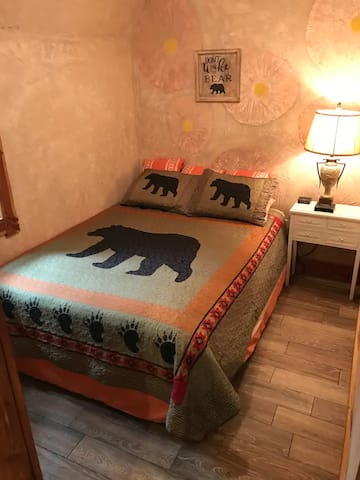 Cozy private bedroom with window has a beautiful new floor and is trimmed with red cedar wood.