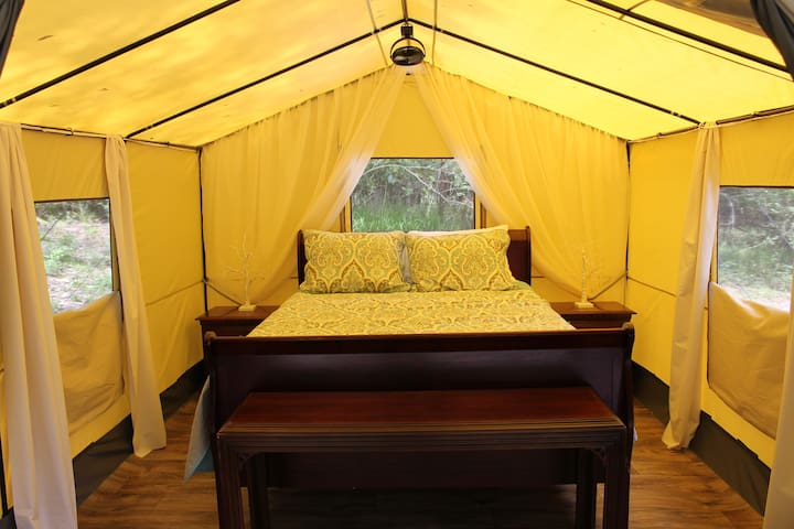 Memory foam mattress on box springs, sheets, pillows, blankets and lights brings comfort to camping!