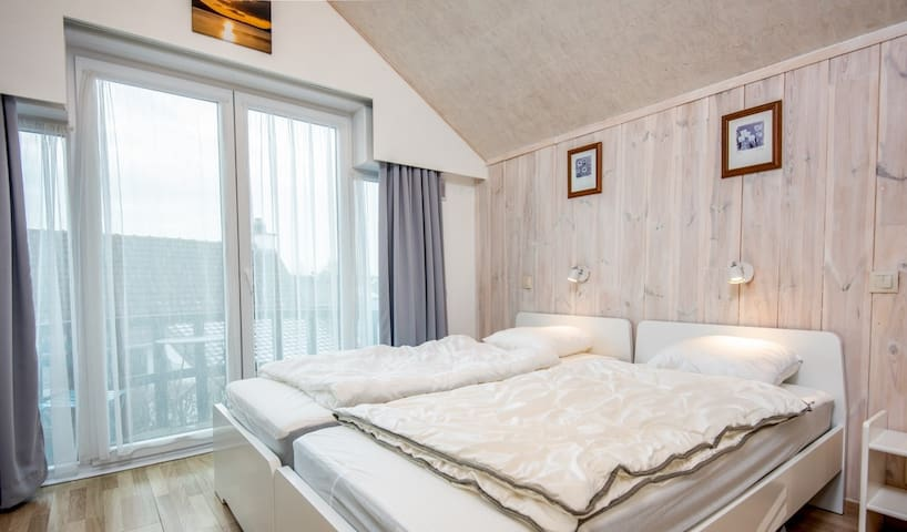 Slaapkamer met 2 éénpersoonsbedden & toegang tot terras (voorzien van tafeltje & 2 stoelen) om heerlijk te aperitieven.