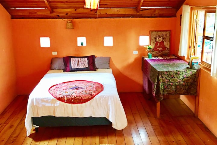 Your serene room with its wooden floor, ceiling and its beautiful window overlooking the jungle!