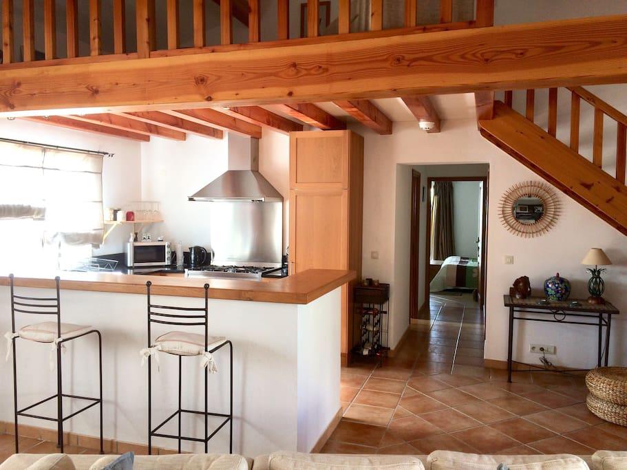 La cuisine sous la mezzanine et le couloir vers la chambre (il comporte salle d'eau et toilettes)