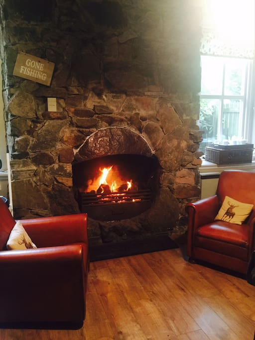 Leather armchairs to cosy up in by the open fire in the kitchen