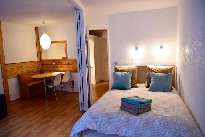 Chambre avec lit double séparée du salon par doubles portes mobiles.