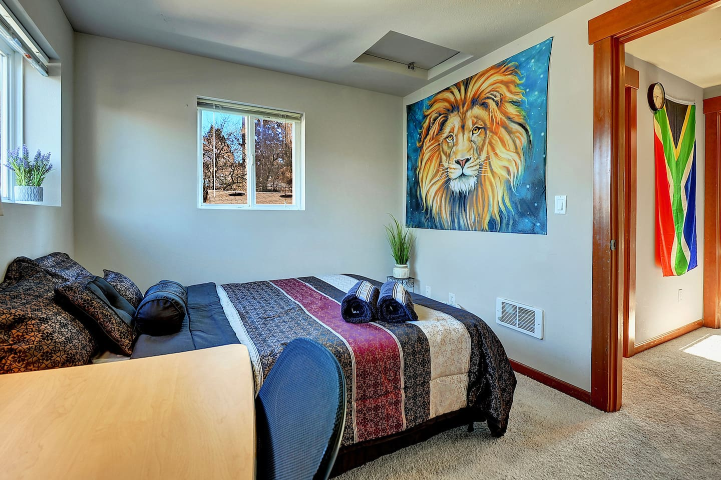 """I dubbed this room the """"Cosmic Lion"""" room, as a tribute to our friendly guardian big cat hanging from the wall. Fresh linens + a comfy queen sized bed = the best sleep you've had in a long time!"""