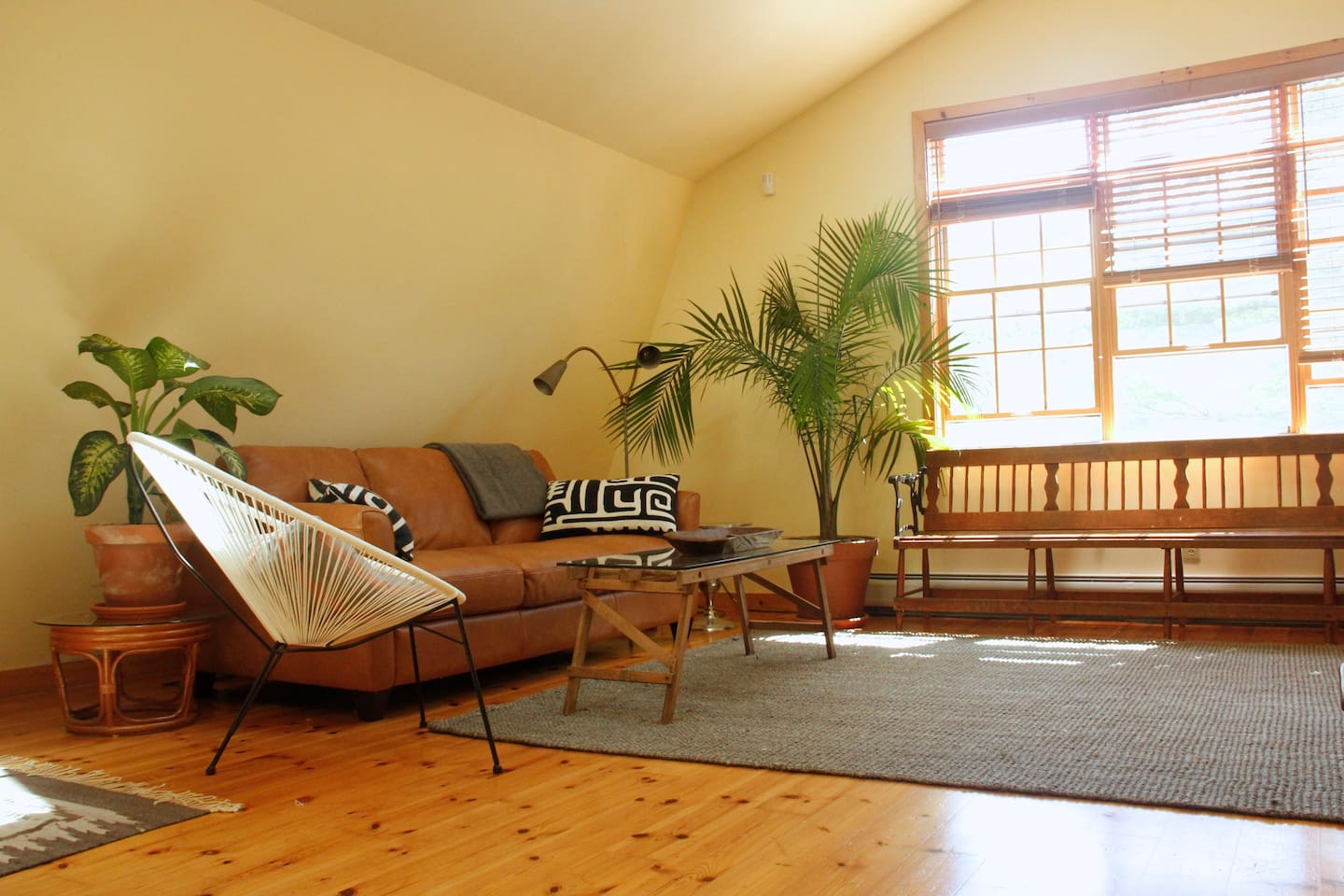 A spacious living room with skylights and a wall of windows that lets in the sound of the brook