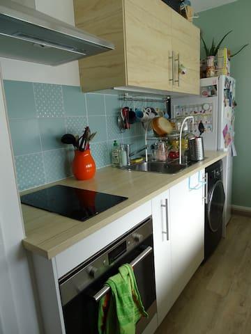 Une hotte, deux plaques électriques, un four, une machine à laver/sèche linge, un réfrigérateur.