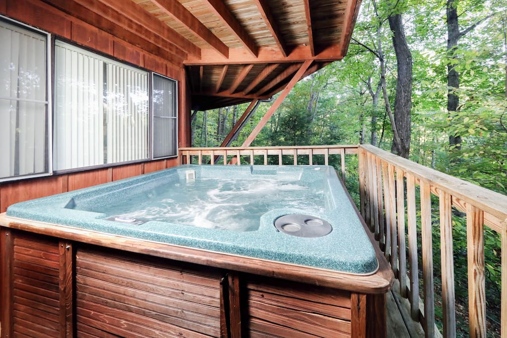 Private hot tub on the lower deck with serene wooded surroundings.