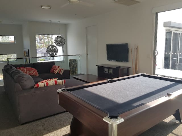 Second floor living room with pool table, double sofa bed, tv, ironing centre and balcony access