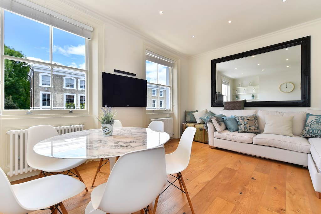 The open plan dinning/living/kitchen area is bright light and spacious with TV and sofa which turns into a double bed.