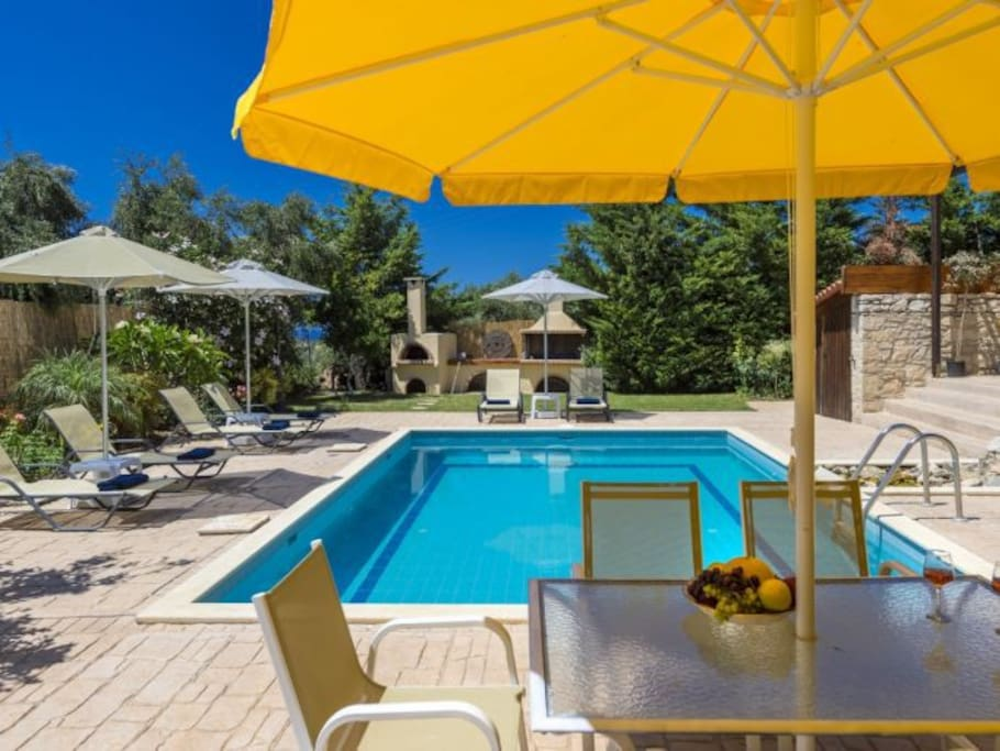 Pool with sun loungers and umbrellas