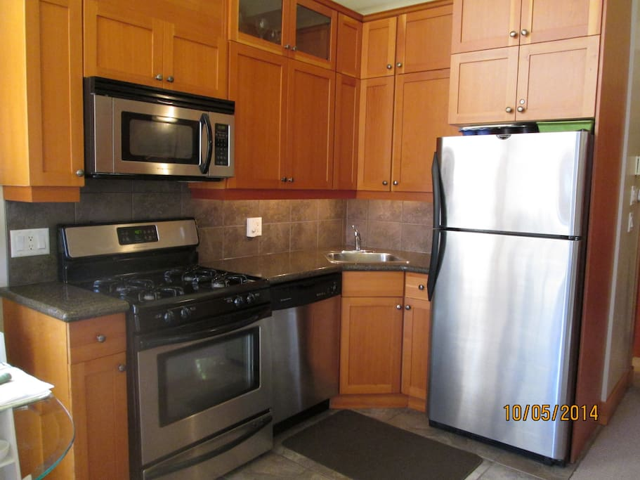 Kitchen area with stainless steel appliances. Heated tile throughout.