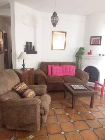 La sala tiene un cómodo love seat  y un sillón individual reclinable con vista al balcón y jardín arbolado.