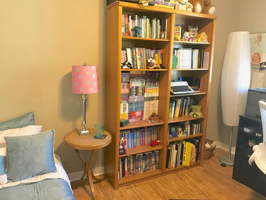 The futon is inside an office with a full bookshelf.
