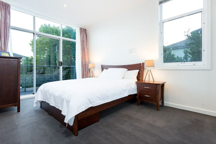 A fourth bedroom comes with a queen bed fitted with luxury linen, dark timber furniture and outdoor access