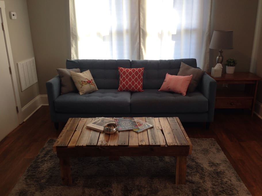 Comfortable couch with custom reclaimed pallet wood coffee table