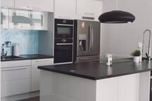 Moderne kjøkken med induksjons topp, innebygd dampovn, stekeovn, mikrobølgeovn og kjøleskap med isbitmaskin og kulsyremaskin.
