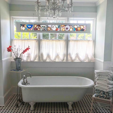 Bathroom was built for this vintage claw foot tub. Adorned with a agaite stained glass window made by an artist from South Carolina.