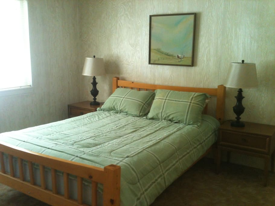 Master bedroom has a queen bed and small attached bathroom.