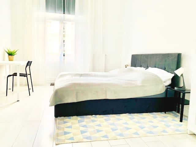 Sypialnia z balkonem. Wyposażona w biurko i szafę. Łóżko o wymiarach 180x200