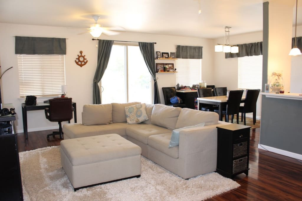Spacious living area with sleeper sofa, area rug, desk, wifi, AppleTV, DVD player, flat screen TV, cable, piano, two ceiling fans and plenty of lighting