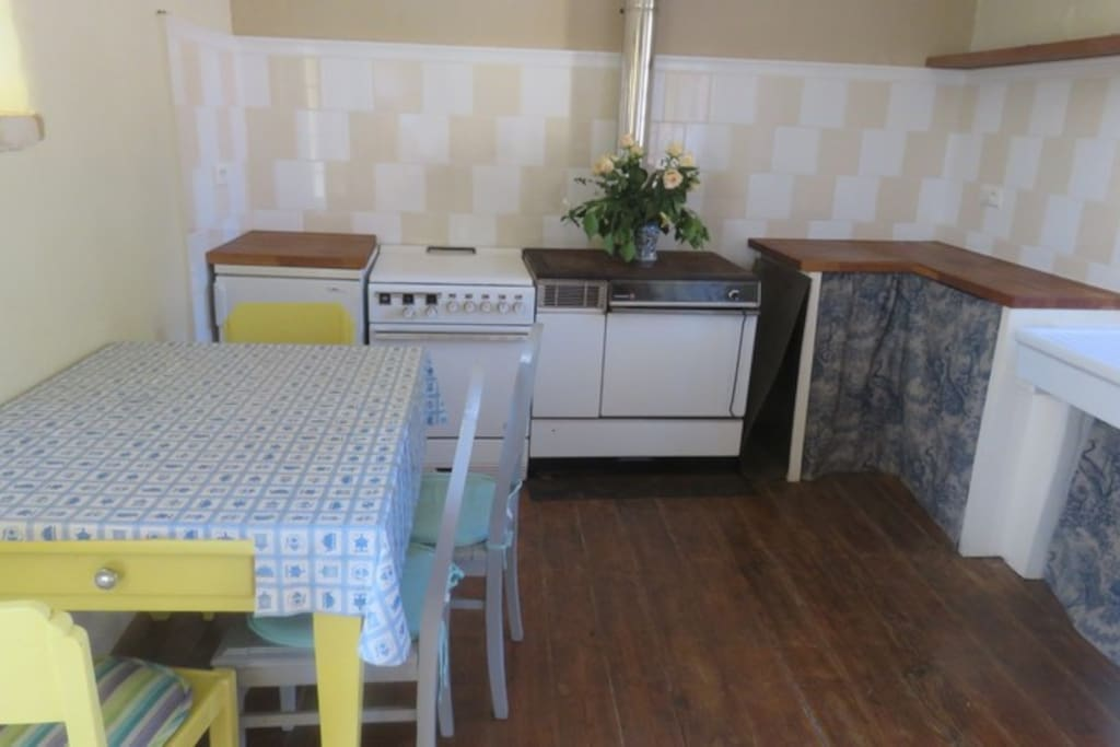 Kitchen with gas cooker, woodburning stove and dishwasher.