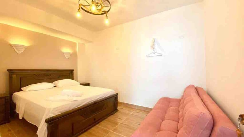 Tercera habitación Ésta queda en frente del jacuzzi, con una ventana de madera, cama Queen, dos mesas de noche, cajón al final de la cama con secador de cabello y plancha para ropa, nichos de luces tenues y luz colonial, sofá cama, aire acondicionado