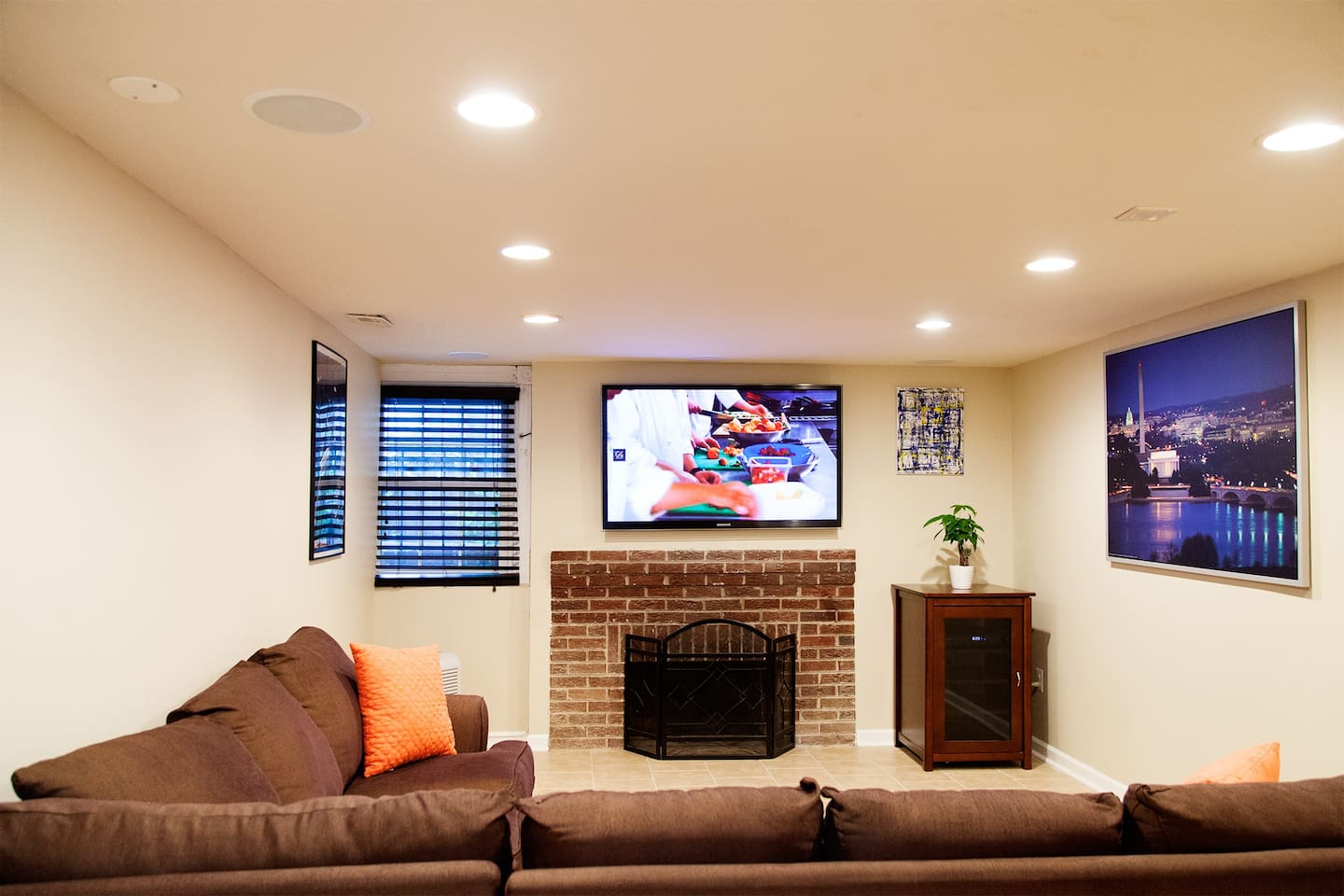 Well lit and spacious living room area with HD TV and surround sound