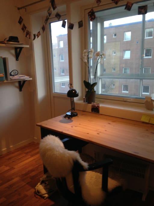 Skrivebord med utsikt ut på veranda og balkong